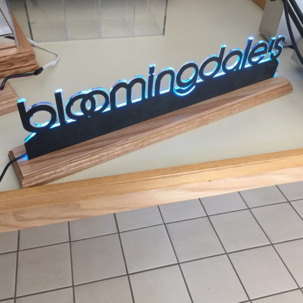 Laser-cut and LED edge-lit acrylic with Black ABS laser-cut face with wood base